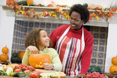 Grandmother and granddaughter on Halloween. Grandmother and granddaughter making jack o lantern on Halloween Royalty Free Stock Images