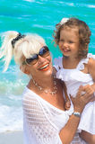Grandmother and granddaughter are having fun on the beach. Grandmother and granddaughter at the beach Royalty Free Stock Image