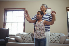Grandmother and granddaughter having fun in living room Stock Photos