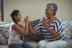Grandmother and granddaughter having fun in living room Royalty Free Stock Images