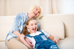 Grandmother and granddaughter having fun together on sofa Royalty Free Stock Image