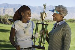 Grandmother and granddaughter holding golf trophy Royalty Free Stock Photo