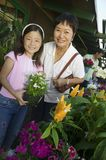 Grandmother and granddaughter holding plant Stock Photos