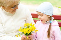 Grandmother with granddaughter. Holding yellow flowers in the park Royalty Free Stock Photo