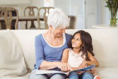Grandmother and granddaughter interacting while looking at photo album in living room. At home Stock Photography