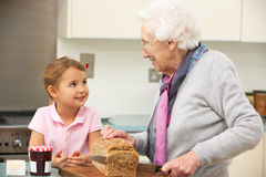 Grandmother and granddaughter in kitchen. Grandmother and granddaughter preparing food in kitchen Stock Images