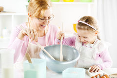 Grandmother and granddaughter in a kitchen. Royalty Free Stock Photography