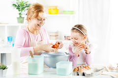 Grandmother and granddaughter in a kitchen. Stock Photos