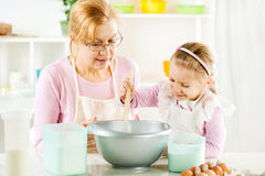 Grandmother and granddaughter in a kitchen. Stock Photo