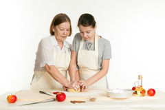 The grandmother and the granddaughter knead dough Stock Photos