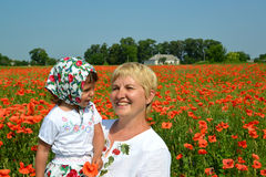 The grandmother and the granddaughter laugh in a poppy field Stock Photos