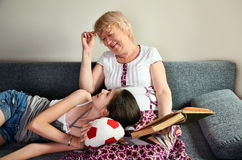 Grandmother and granddaughter laughing sit on the couch and look. Ing at each other horizontal Royalty Free Stock Photos