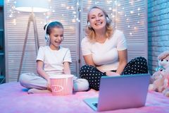 Grandmother and granddaughter are laughing watching movie at night at home. Grandmother and granddaughter are laughing watching movie on laptop at night at home Stock Photo