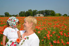 The grandmother and the granddaughter look at each other in the middle of a poppy field Stock Photography