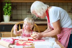 Grandmother and granddaughter making cookies together. Loving caring grandmother, beautiful senior woman, baking tasty sweet cookies together with her Royalty Free Stock Photography
