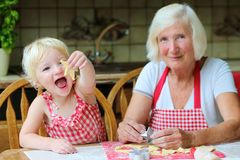 Grandmother and granddaughter making cookies together. Loving caring grandmother, beautiful senior woman, baking tasty sweet cookies together with her Stock Photo