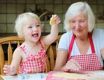 Grandmother and granddaughter making cookies together Stock Photography