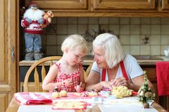 Grandmother and granddaughter making cookies together Royalty Free Stock Image