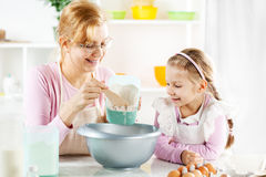 Grandmother and granddaughter making Dough Stock Photos