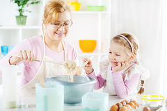 Grandmother and granddaughter making Dough Stock Images
