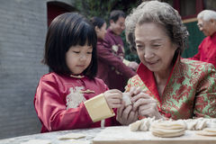 Grandmother and granddaughter making dumplings in traditional clothing Royalty Free Stock Images