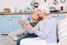 Grandmother and granddaughter making selfie photos. Senior and new generation choose new technologies. Grandmother and granddaughter making self-photos, selfies Royalty Free Stock Images