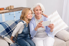 Grandmother and granddaughter making selfie photos. Granddaughter taught grandmother how to make self-photos, selfies on mobile or smart phone. Pretty ladies Royalty Free Stock Photos