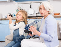 Grandmother and granddaughter making selfie photos. Technologies unite younger and older generations. Grandmother and granddaughter try to understand gadgets Stock Images