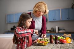 Grandmother and cute granddaughter cooking salad. Grandmother and granddaughter mixing salad with spoon. Being in cozy kitchen Stock Photos