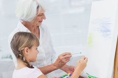 Grandmother and granddaughter painting together Stock Image
