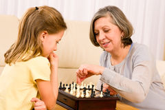 Grandmother and granddaughter play chess together. Grandmother and young girl playing chess together at home Royalty Free Stock Photography