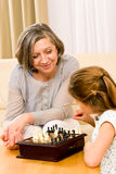 Grandmother and granddaughter play chess together. Young girl playing chess with grandmother together at home Royalty Free Stock Photos