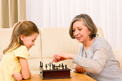 Grandmother and granddaughter play chess together Stock Images