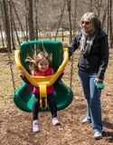 Grandmother and granddaughter play in plastic swing Stock Image