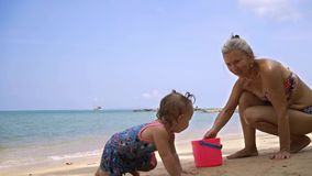 Grandmother and granddaughter play in the sand on the beach with beach toys. A little girl crawls along the beach stock video
