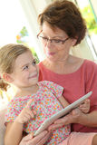 Grandmother and granddaughter playing on a tablet stock photography