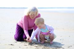 Grandmother and granddaughter playing together on the beach. Happy grandmother playing with her granddaughter, cute toddler girl, at the beach drawing on the Stock Photo