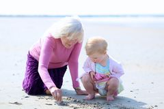 Grandmother and granddaughter playing together on the beach. Happy grandmother playing with her granddaughter, cute toddler girl, at the beach drawing on the Royalty Free Stock Images