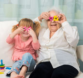 Grandmother with granddaughter playing toys Stock Images