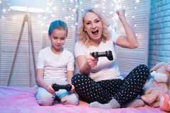 Grandmother and granddaughter are playing video games at night at home. Woman is winning. stock image