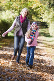 Grandmother and granddaughter playing in woods. Grandmother and granddaughter playing in autumn woods Stock Photography