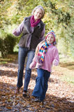 Grandmother and granddaughter playing in woods. Grandmother and granddaughter playing in autumn woods Stock Image