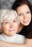 Grandmother and granddaughter portrait. Embraced  and smiling at camera Royalty Free Stock Photo