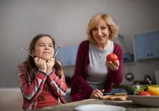 Grandmother and cute granddaughter cooking salad. Grandmother and granddaughter posing on camera. Granny showing tomato and girl palying with spoons Royalty Free Stock Images