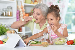 Grandmother and granddaughter preparing dinner. On table with tablet Stock Photography