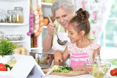 Grandmother and granddaughter preparing dinner. On table with tablet Royalty Free Stock Photography