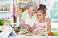 Grandmother and granddaughter preparing dinner. On table with tablet Royalty Free Stock Image