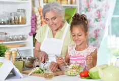 Grandmother and granddaughter preparing dinner. On table with tablet Royalty Free Stock Photo