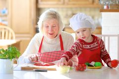 Grandmother and granddaughter preparing pizza. Happy family, grandmother with her granddaughter, adorable little girl, preparing delicious pizza together topping Stock Photos