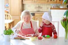 Grandmother and granddaughter preparing pizza Stock Images